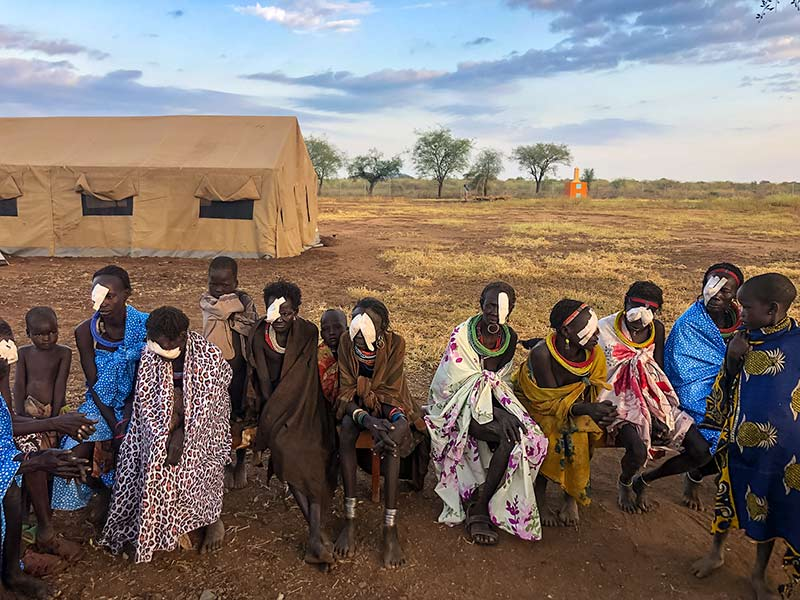 Adult patients wearing eye bandages post-surgery and their children sitting in front of a large brown tent.
