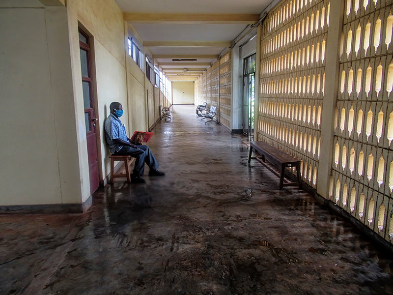 Male patient, wearing a face mask, sitting alone on a bench in a hospital corridor.