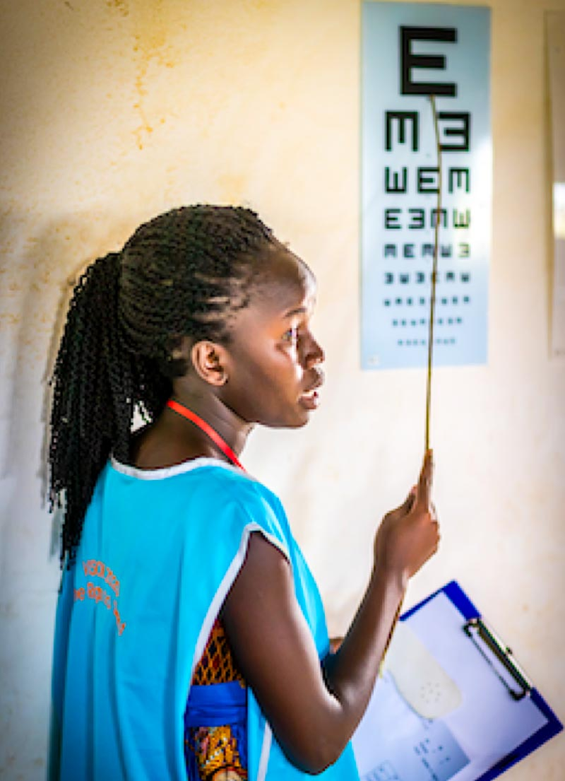 Female eye care worker pointing with a stick to a tumbling E chart