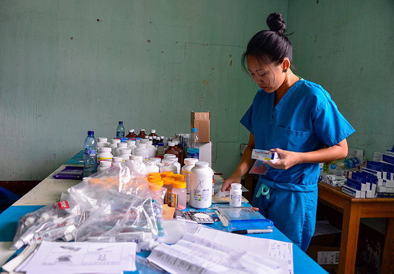 A female pharmacist standing at a table full of medicines, sorting them