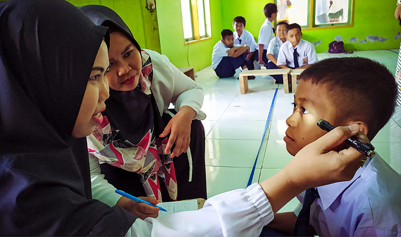 Two female eye care workers examining a boy's eyes in a classroom using a torch