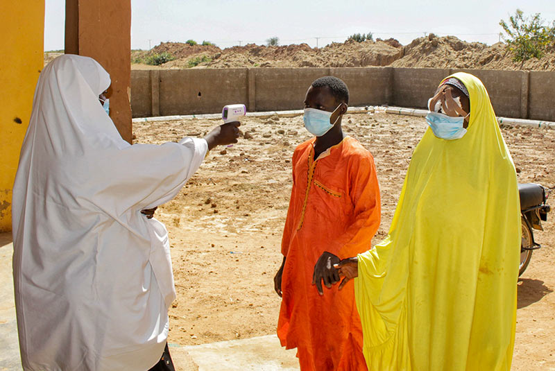 A female health worker points an infrared thermometer towards the forehead of a female patient arriving at the clinic with her male relative escort