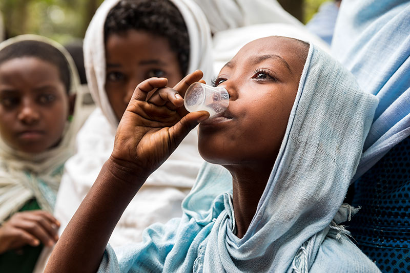 Young girl drinking azithromycin oral suspension from a clear plastic cup