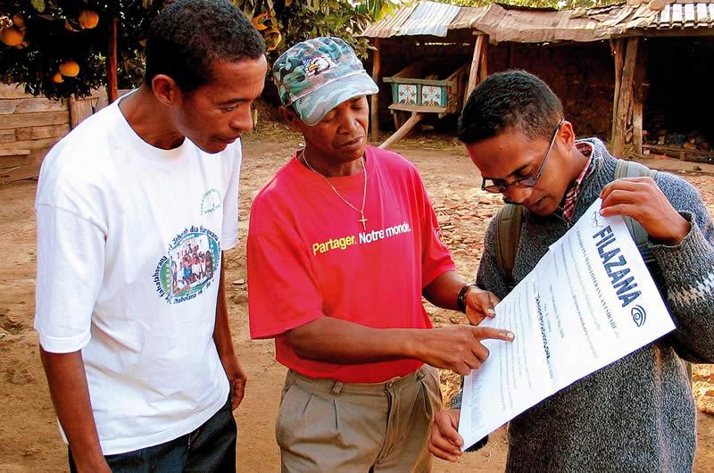 Un chef de Fokontany reçoit les affichages de sensibilisation des mains de deux agents de santé oculaire communautaire. MADAGASCAR. © Henry Nkumbe