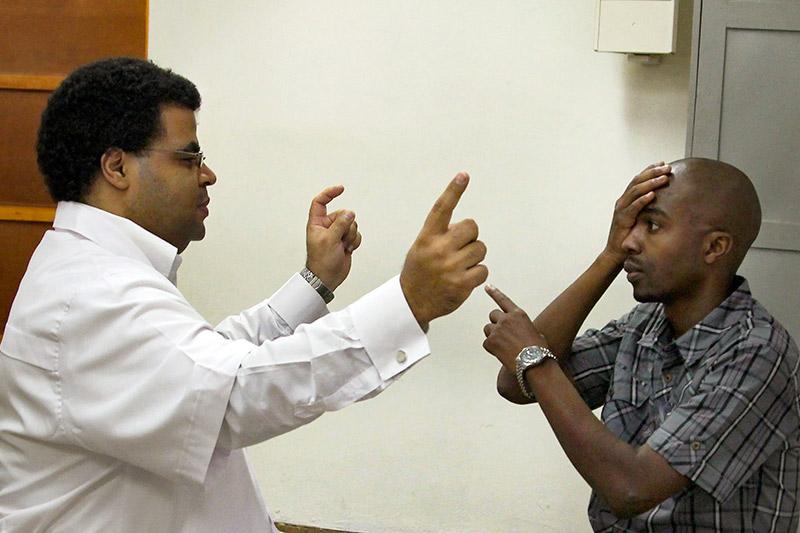 Un agent de santé est assis face à un patient et tient ses deux index écartés. Le patient couvre un œil d'une main et pointe vers un des index avec l'autre main.