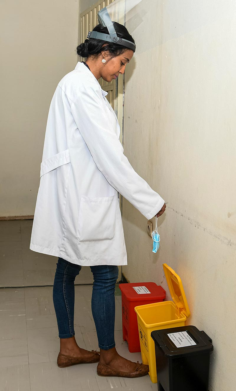 A memeber of staff wearing a white coat and a visor, removes her face mask and drops it into a yellow pedal bin