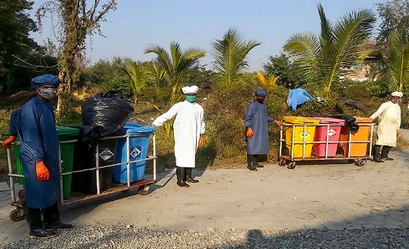 Four hospital staff members wearing PPE pull trolleys loaded with waste in different colour coded bins
