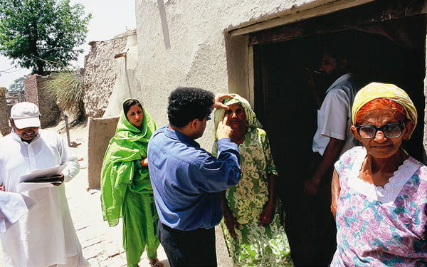 Examining eyes door to door in a village. PAKISTAN. © Jamshyd Masud/Sightsavers.
