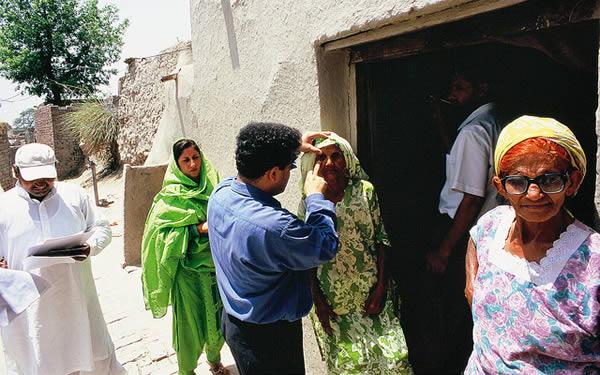 Examining eyes door to door in a village. PAKISTAN. © Jamshyd Masud/Sightsavers.