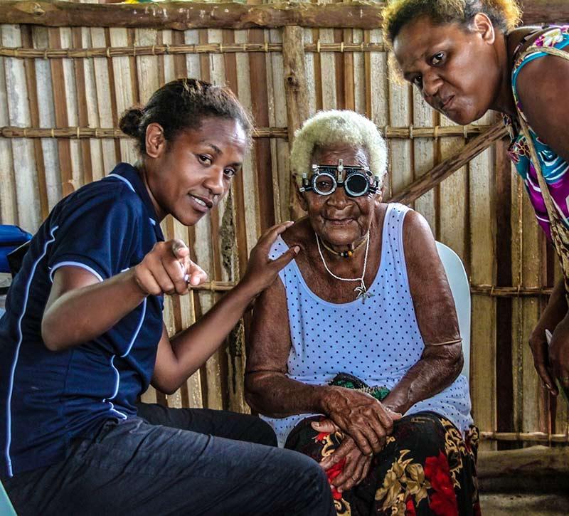 Une patiente âgée portant des montures d'essai est assise durant un test de vision. Deux agentes de santé se penchent vers elle, et l'une d'elles pointe du doigt ce que regarde la patiente.