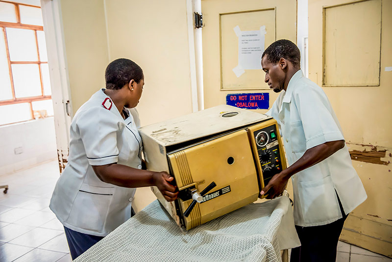 A male and a female colleague lift a heavy piece of equipment from a trolley together